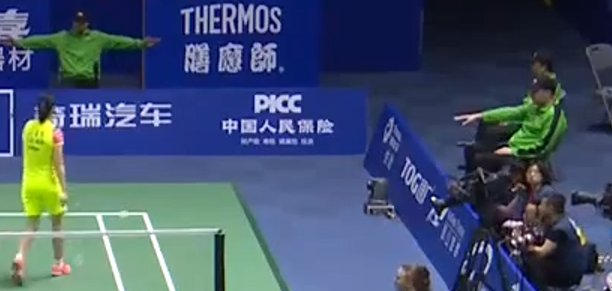 Two line judges showing different signs